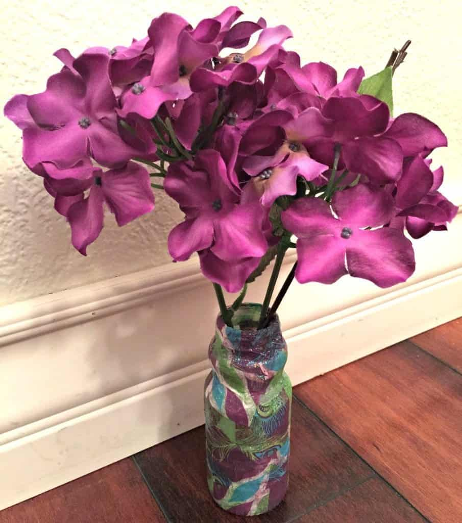 Spring Plastic Bottle Tissue Paper Craft. This super easy craft only requires a plastic bottle, tissue paper and glue. This craft also makes for the perfect Mother's Day or Teacher Appreciation Day gift.