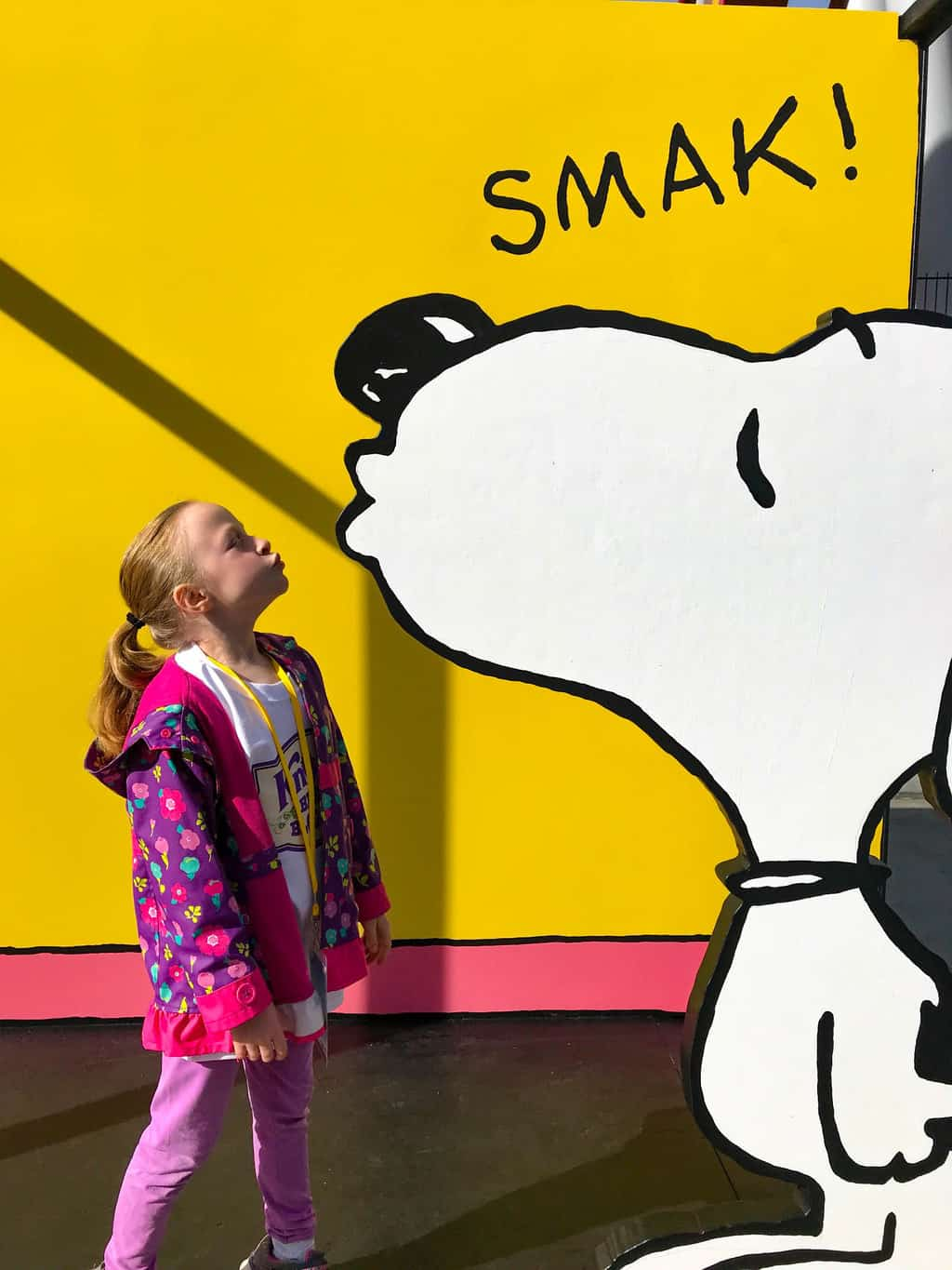 Young girl taking a picture with Snoopy during the Peanuts Celebration at Knott's Berry Farm.
