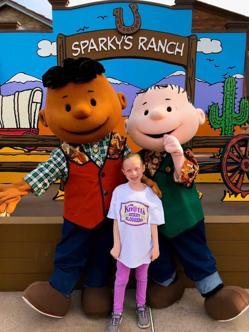 Girl taking a picture with Peanuts Gang characters at Knott's Berry Farm.