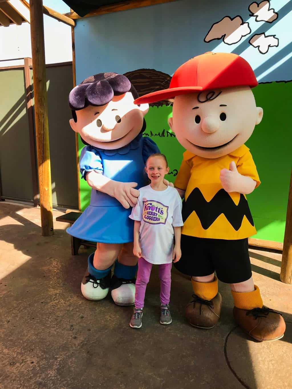 Girl talking a picture with Lucy and Charlie Brown during Peanuts Festival at Knott's.