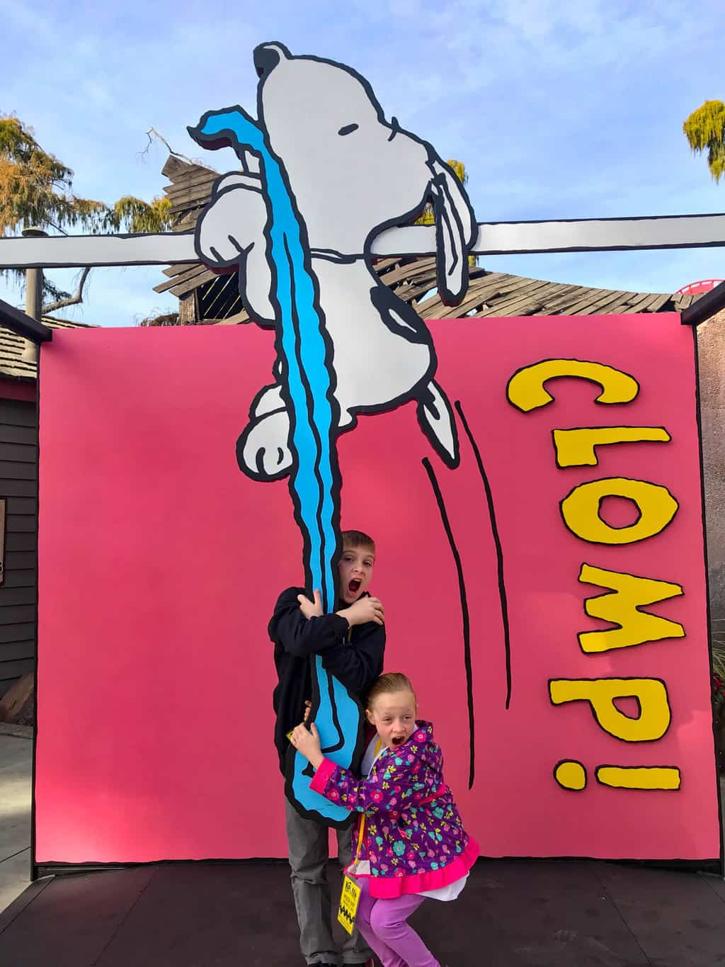 Boy and girl taking a picture with Snoopy at Knott's Berry Farm Peanuts Celebration.