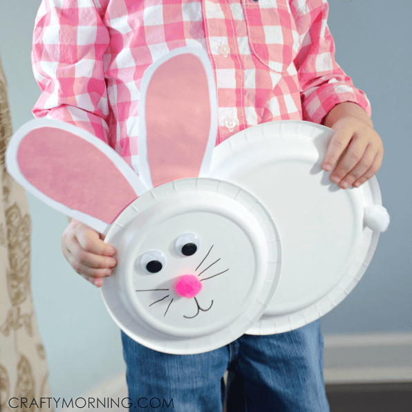 kid holding a pink and white paper plate bunny craft
