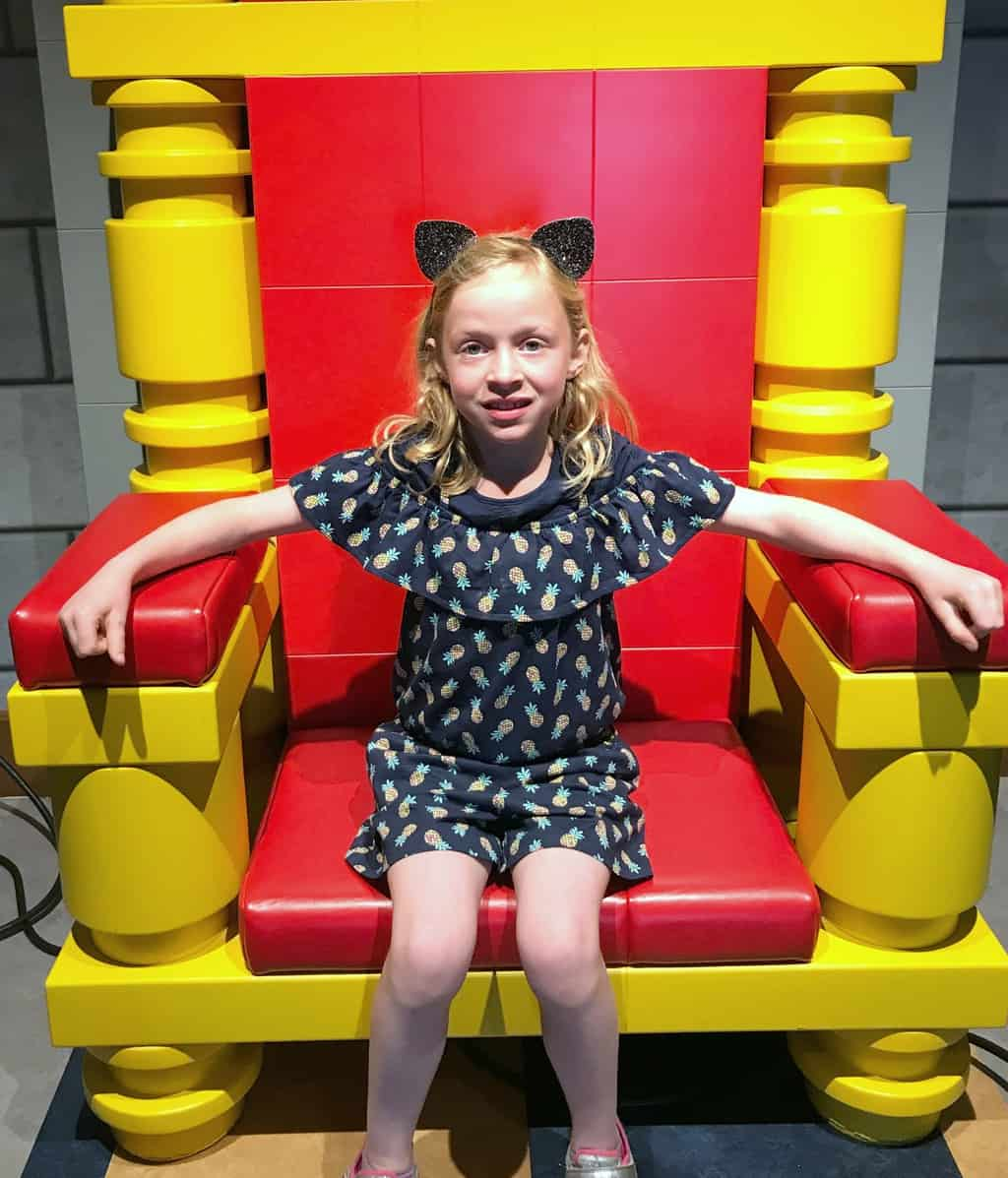 Girl sitting in royal chair inside the LEGOLAND Castle Hotel in California