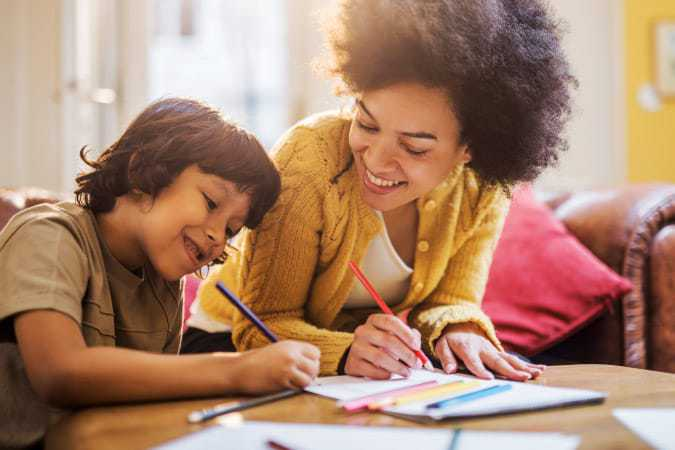 A boy being homeschooled by his mom through the Biola Youth Academics program