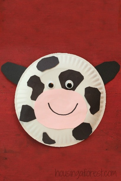 easy black and white spotted cow craft for kids made out of a paper plate