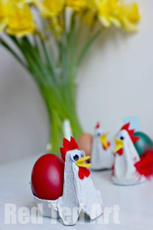 easy chicken craft for preschool made out of a egg carton and red feathers