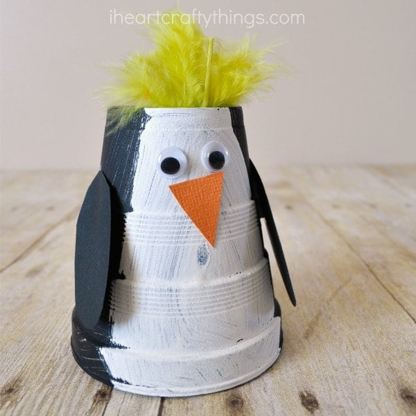 children's penguin craft made out of a paper cup and paint