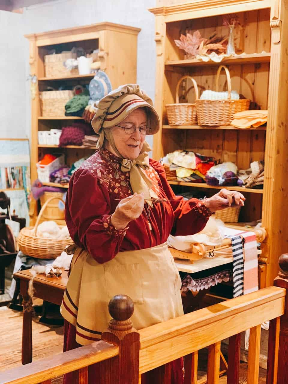 A lady spinning yarn at Gertrude's Dress Shop at Knotts