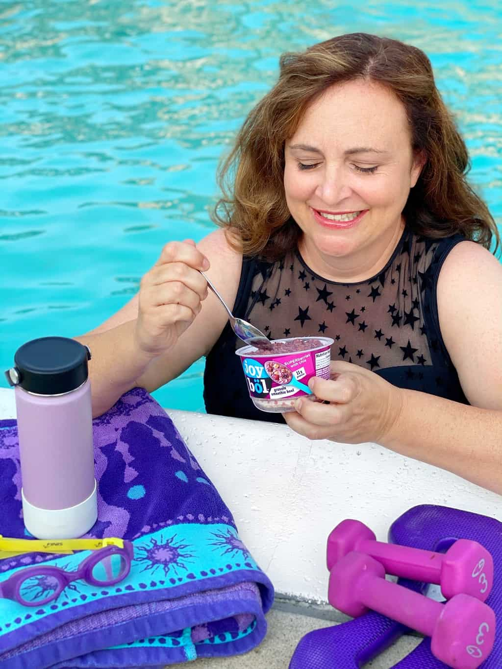 a woman eating joybol after working out in the pool